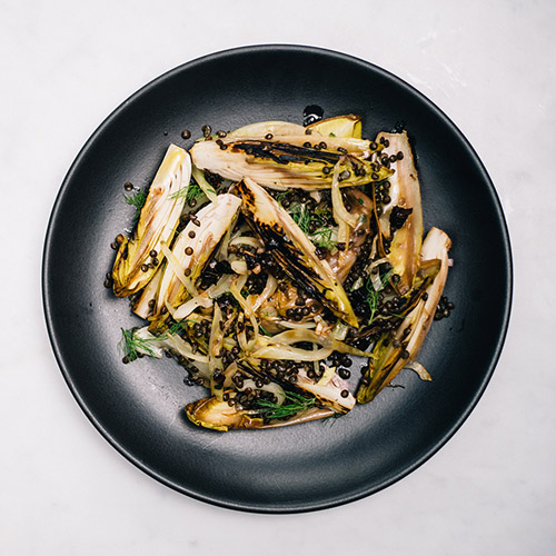 <p>Charring endive and fennel gives texture and flavor to a healthy winter lentil salad while dried prunes add sweetness to counter the sharp edge of the shallot vinaigrette.</p>